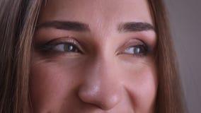 Всход крупного плана молодой красивой женской стороны с глазами смотря к стороне с усмехаясь выражением лица акции видеоматериалы