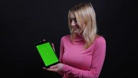 Всход крупного плана молодой милой белокурой женщины используя планшет и показывать зеленый экран chroma к камере с предпосылкой сток-видео