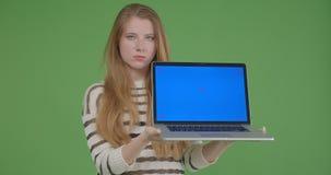 Всход крупного плана молодой милой кавказской женщины используя ноутбук и показывать голубой экран к камере акции видеоматериалы