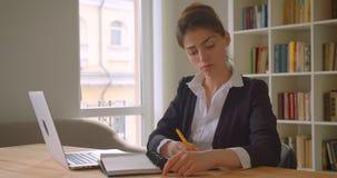 Всход крупного плана молодой милой кавказской коммерсантки используя ноутбук и принимающ примечания смотря камеру в офис сток-видео
