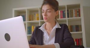 Всход крупного плана молодой милой кавказской коммерсантки используя ноутбук и поворачивающ к камере в офис внутри помещения видеоматериал