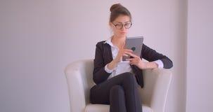 Всход крупного плана молодой милой кавказской коммерсантки используя планшет сидя в кресле смотря усмехаться камеры видеоматериал