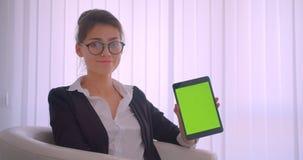 Всход крупного плана молодой милой кавказской коммерсантки используя планшет и показывающ зеленому chroma ключевой экран к камере акции видеоматериалы