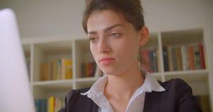 Всход крупного плана молодой милой кавказской коммерсантки работая на ноутбуке и поворачивая к камере в офисе внутри помещения сток-видео