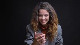 Всход крупного плана молодой привлекательной кавказской женщины имея видео- звонок по телефону жизнерадостно усмехаясь перед стоковое фото