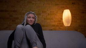 Всход крупного плана молодой привлекательной кавказской женщины хипстера смотря фильм hprror по телевизору и получая вспугнутое у видеоматериал
