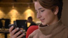 Всход крупного плана молодой привлекательной кавказской коммерсантки просматривая по телефону и усмехаясь жизнерадостно внутри по стоковые изображения rf
