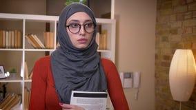 Всход крупного плана молодой привлекательной мусульманской студентки в hijab и стекел держа книгу стоя внутри помещения в видеоматериал