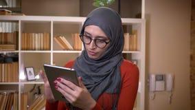 Всход крупного плана молодой привлекательной мусульманской студентки в hijab просматривая на планшете смотря вперед и усмехаясь видеоматериал
