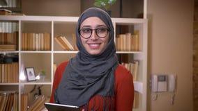Всход крупного плана молодой привлекательной мусульманской студентки в hijab используя планшет усмехаясь счастливо стоящий внутри акции видеоматериалы