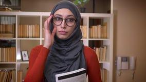 Всход крупного плана молодой привлекательной мусульманской студентки в hijab исправляя ее стекла и держа книгу стоя внутри помеще видеоматериал