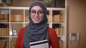 Всход крупного плана молодой привлекательной мусульманской студентки в hijab исправляя ее стекла и держа книгу усмехаясь счастлив сток-видео