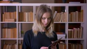 Всход крупного плана молодой привлекательной студентки используя планшет и показывающ зеленый экран chroma к камере внутри помеще акции видеоматериалы