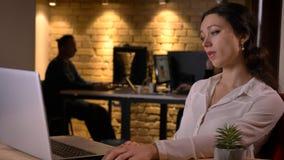 Всход крупного плана молодой пробуренной кавказской коммерсантки печатая на ноутбуке и быть неработоспособный внутри помещения на стоковая фотография rf