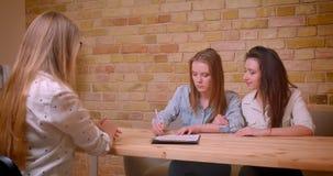 Всход крупного плана молодых красивых лесбосских пар говоря с женским риэлтором о приобретении квартиры сидя  видеоматериал