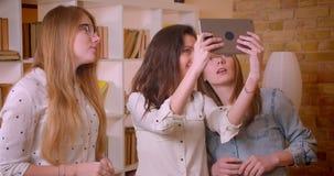Всход крупного плана молодых красивых лесбосских пар говоря с женским риэлтором о покупать квартиру используя планшет акции видеоматериалы