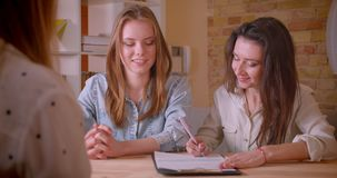 Всход крупного плана молодых красивых лесбосских пар говоря с женским риэлтором о приобретении квартиры подписывая a видеоматериал