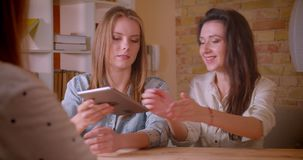 Всход крупного плана молодых красивых лесбосских пар говоря с женским риэлтором с планшетом о приобретении квартиры видеоматериал