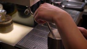 Всход крупного плана молока barista кипя в серебряном кувшине используя раковину 3-отсека в кафе внутри помещения сток-видео