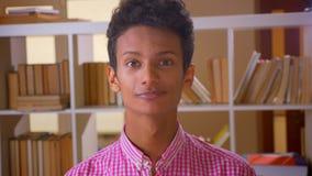 Всход крупного плана мужчины молодого attractice индийского кивая и смотря камерой в библиотеке колледжа внутри помещения видеоматериал