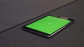 Всход крупного плана планшета с зеленым экраном chroma с применением для разрабатывает отслеживать лежать на поле в видеоматериал