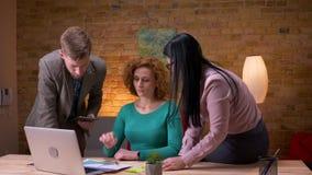 Всход крупного плана 3 работников офиса обсуждая данные используя планшет и диаграммы ноутбука споря внутри помещения на видеоматериал