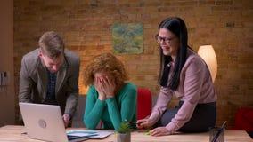Всход крупного плана 3 работников офиса обсуждая данные используя планшет и диаграммы ноутбука смеясь счастливо внутри помещения  сток-видео