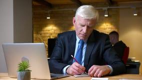 Всход крупного плана старого кавказского бизнесмена используя ноутбук и принимающ примечания внутри помещения в офис на рабочем м сток-видео