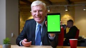 Всход крупного плана старого кавказского бизнесмена используя планшет и показывающ зеленый экран chroma к камере внутри помещения видеоматериал