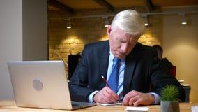 Всход крупного плана старого кавказского бизнесмена работая на ноутбуке и принимая примечания внутри помещения в офис на рабочем  сток-видео