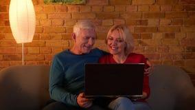 Всход крупного плана старших счастливых пар используя социальные средства массовой информации на ноутбуке усмехаясь жизнерадостно акции видеоматериалы