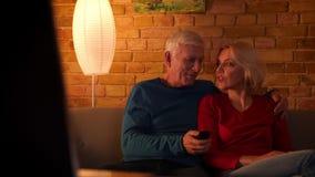 Всход крупного плана старших счастливых пар смотря тв-шоу усмехнуться жизнерадостно и обняться совместно сидеть на кресле сток-видео