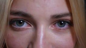 Всход крупного плана стороны молодого милого белокурого кавказца женской с голубыми глазами смотря прямо на камере с очаровывать видеоматериал