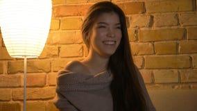 Всход Closdeup молодой милой кавказской женщины смотря комедию по телевизору и усмехаясь жизнерадостно на уютном доме внутри поме стоковые фото