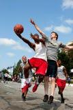 Всходы человека против защитника в напольном турнире баскетбола улицы Стоковое фото RF