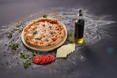Вся итальянская очень вкусная свежая пицца с томатом и pepperoni на темной предпосылке Пицца на черной таблице с ингридиентами Стоковые Изображения
