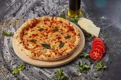 Вся итальянская очень вкусная свежая пицца с томатом и pepperoni на темной предпосылке Пицца на черной таблице с ингридиентами Стоковая Фотография RF