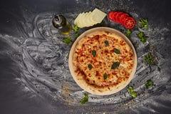 Вся итальянская очень вкусная свежая пицца с томатом и pepperoni на темной предпосылке Пицца на черной таблице с ингридиентами Стоковое Фото
