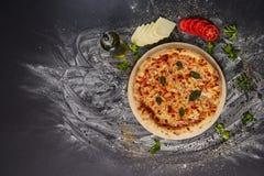 Вся итальянская очень вкусная свежая пицца с томатом и pepperoni на темной предпосылке Пицца на черной таблице с ингридиентами Стоковое Изображение