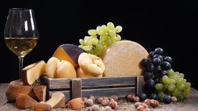 Вся круглая головка сыра пармезана или пармезана трудного, виноградин в деревянной коробке и красного вина Серии гаек или фундука акции видеоматериалы