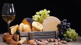 Вся круглая головка сыра пармезана или пармезана трудного, виноградин в деревянной коробке и красного вина Серии гаек или фундука сток-видео