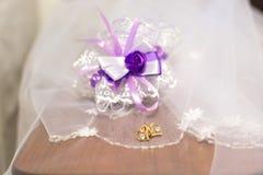 Вуаль, серьги, и подвязка с фиолетовым смычком Стоковое Фото