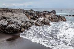 Вулканическая порода на пляже отработанной формовочной смеси в Padangbai, острове Бали, Индонезии Стоковое Фото