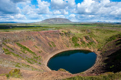 Вулканический кратер Kerid с голубым озером внутрь, на солнечном дне с красивым небом, Исландия Стоковое фото RF