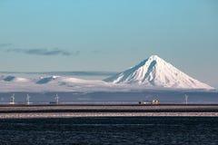 Вулкан на Камчатском полуострове, и электрические станции энергии ветра на береге моря Стоковое Фото