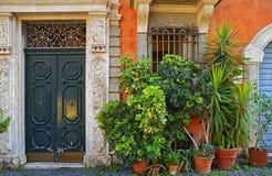 Входная дверь в дворе дома, красивое крылечко украшенное с цветками стоковая фотография rf