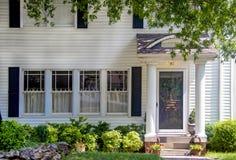 Вход очаровательного белого деревянного дома с столбцами на крылечке и красивых благоустраивая и свисая ветвях и красном белом и стоковое фото rf