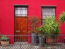 Входная дверь и окно к крылечку Яркие цветы Стоковые Фотографии RF