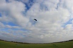 Входящий skydiver, облачные небеса над ясными полями на красивый день стоковое фото rf