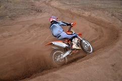 Вход для того чтобы повернуть песочного гонщика следа мотоцикла w motocross Стоковые Фотографии RF